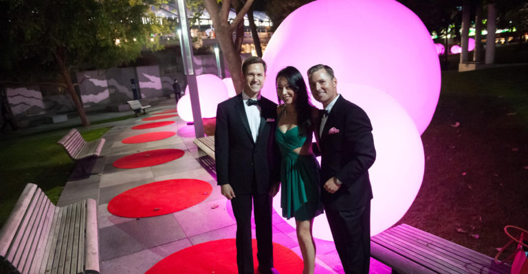 A formally-dressed group poses in front of a giant round purple light fixture