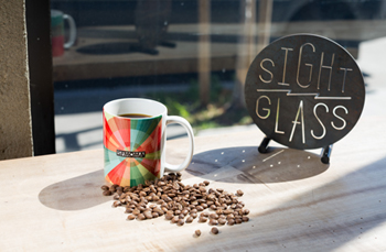 """A mug of coffee with the SFMOMA logo, next to a pile of coffee beans and a sign reading """"Sight Glass"""""""