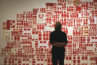 A woman looks at a graphic red and white wall painting