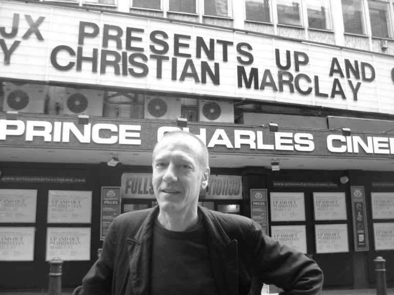 Christian Marclay stands in front of a theater marquee bearing his name