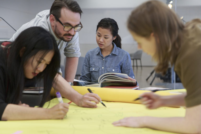 A group of adults write on a large roll of paper