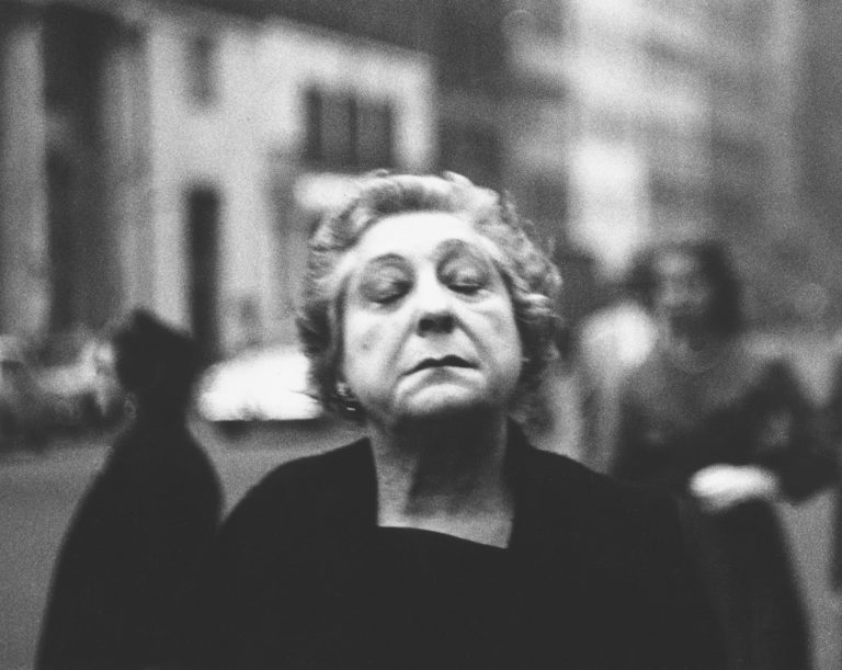 A photograph of a woman on the street with her eyes closed