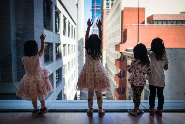 Four little girls looking out towards Natoma street from inside the museum