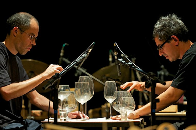 Two men play a modified glass harmonica made of wine glasses with directional microscopes