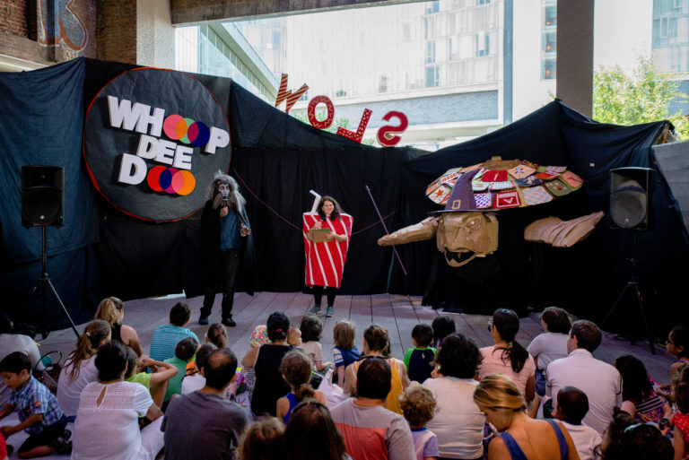 """Performers dressed as a werewolf and a soda can on a stage with a large witchy puppet and a sign reading, """"Whoop Dee Doo"""" behind"""
