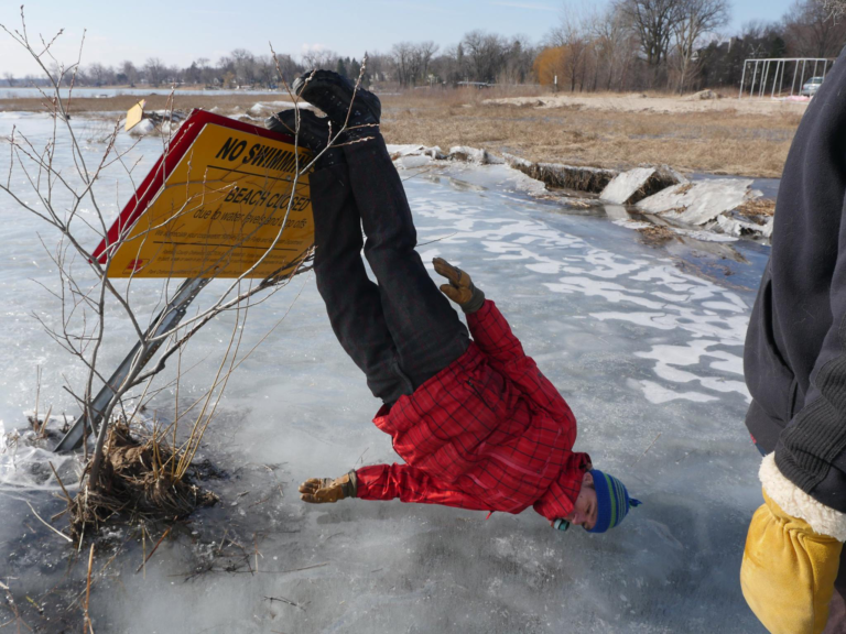 """A man leaning upside down on a """"no swimming"""" sign on a frozen lake"""