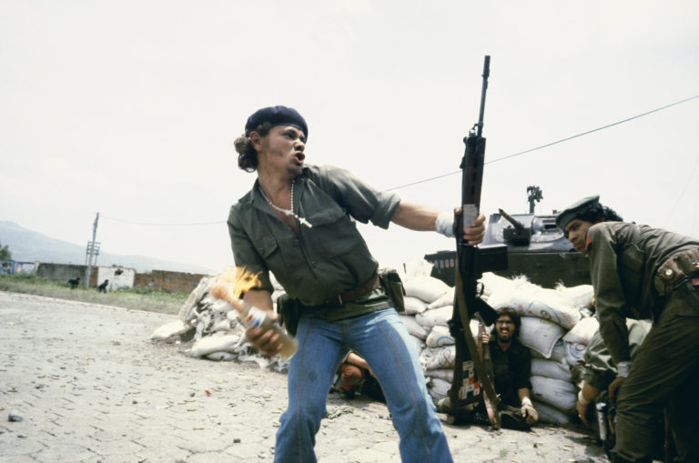 A man in a beret holding a rifle in one hand and throwing a Molotov cocktail made of a Pepsi bottle, with other men in uniform and a tank behind him