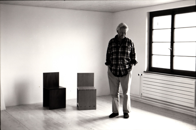 Black and white photograph of a man standing next to square, modernist chairs