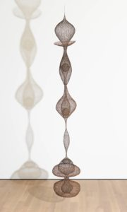 "This vertical hanging sculpture is almost eleven feet tall, and features six lobes of delicate ""crocheted' mesh, crafted with wire made from iron, copper, and brass. The continuous, undulating form resembles a mesh tube that has been pinched in some places, and stretched in others, to create a series of symmetrical, but irregularly sized orbs. Some of the resulting shapes resemble bulbous onions, almost two feet in diameter, with domed tops that taper to a point. Others are much thinner, like elongated cocoons that taper at both ends to a width of mere inches. The uppermost lobe has an onion-dome top, and a collar at its base that is shaped like a tea cup saucer. Beneath that, near the middle of the sculpture, are two orbs with multiple layers. Each contains a second pod with a wire mesh sphere inside, not unlike a yoke inside an egg, floating in a basket. A long, stretched cocoon of wire mesh hangs beneath the first three lobes, linking them to a cluster of orbs at the bottom of the sculpture. These overlapping shapes resemble two distorted hourglasses. A single sphere is suspended inside the top lobe of this bottom grouping."