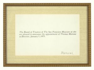 Inside a delicate wooden frame with gold trim and a golden linen mat is a small announcement card featuring three lines of italicized text. It reads: The Board of Trustees of the San Francisco Museum of Art are pleased to announce the appointment of Thomas Marioni as Director, January 3, 1973.  In the bottom right hand corner of the card, the artist, Tom Marioni, has signed his last name in pencil.