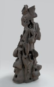 This clay sculpture stands four and a half feet tall, is two and a half feet wide at its base, and is vaguely conical in shape. It resembles a gray desert hoodoo: a tall spire of rock, eroded into an irregular shape over time. The bottom portion of the sculpture features small caves and closed-in rooms with rough windows, giving the sculpture the appearance of a haphazard termite mound. Near the middle of the piece, the rooms and caves begin to stretch and distort, and resemble sagging, gaping mouths. Near the top, the caves and clay shapes become more abstract and decorative. Some of the stacked elements resemble crude masks or helmets, while others resemble melting bowls.