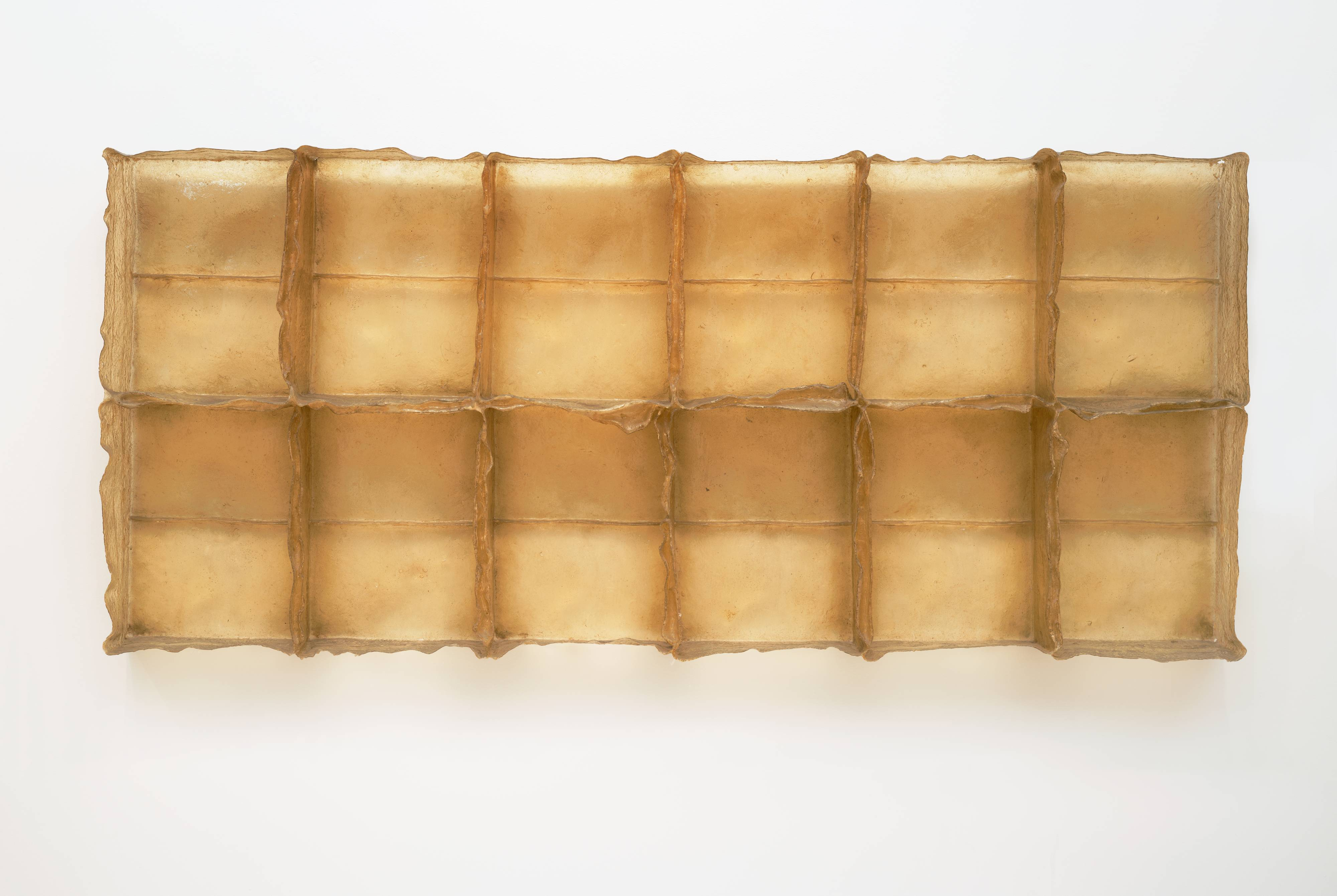 This golden-yellow sculpture resembles a giant ice cube tray hanging horizontally on a wall, with the open, empty, rectangular niches facing us. The piece is more than three feet tall and over seven feet long with six niches on top and six on the bottom. Each individual compartment is divided in two by a thin horizontal line, giving the impression that there are, in fact, four rows of rectangles. The piece is constructed of fiberglass and polyester resin, giving it the look of golden honeycomb. The edges of the open boxes are imperfect and ragged, like peeling skin, in contrast to the structure itself, which is precise and orderly.