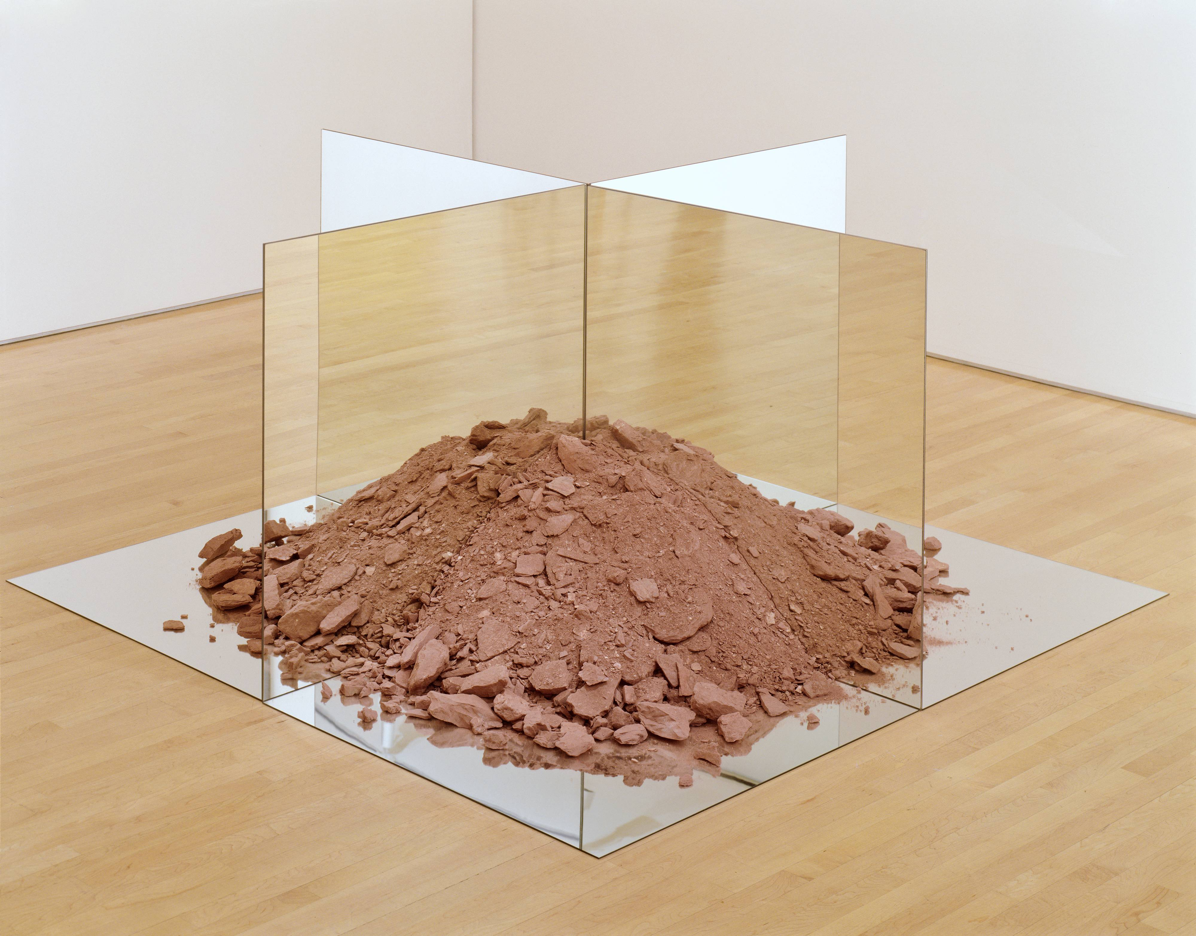 <p>The base of this sculpture is a six foot square mirror lying flat on the floor. Standing upright on top of it are four three foot square double-sided mirrors which form a cross, dividing the base into equal quadrants. Inside the resulting spaces are piles of dry terra-cotta soil, heaped up toward the apex of the mirrored walls. Although each section only houses one quarter of a mound of soil, the mound looks complete from every angle, due to the reflections in the mirrored walls. The sandy red soil is full of red stones, and resembles crushed bricks. None of the mirrored panels have frames or visible supports; they appear to be supported solely by the mounds of soil.</p>