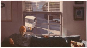 In this self-portrait, photorealist painter Robert Bechtle sits on a couch under a large window, facing us. The pillowed back and fabric-covered arms of the blue couch stretch across the bottom of the five-and-a-half-foot wide, three-foot tall canvas. Bechtel sits on our left with one elbow on the armrest and the other arm draped across the back of the couch. He has a grey beard, close-cropped hair at the temples of his otherwise bald head, and wears a blue sweater. A pair of glasses rests on his chest, hanging down from a thin cord that loops around the back of his neck. On the other end of the couch, at our lower right, sits a pillow resembling a repurposed potato sack that reads 'Potero Hill'. Centered above the couch is a window offering views to the neighbourhood street outside. The six square panes at the bottom are unobscured, but the panes near the top of the window are partially covered by thin, white, horizontal blinds. Outside, a steep hill runs from our bottom right toward the upper left. A silver sedan is parked across the street, and a boxy, off-kilter station wagon sits parked behind Bechtel, perpendicular to the hill. The diagonal lines and odd angles of the outside world lie in contrast to those found inside, in the trim of the window panes, the precise blinds, and the back of the couch.