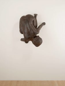 This life-sized bronze sculpture depicts a small nude woman creeping down the wall like Spiderman, defying gravity. Curled up with her knees under her body, her rear end aimed at the ceiling, and her breasts pointing toward the wall, she glances back over her left shoulder with piercing glass eyes and a steely gaze. Her cast bronze body is dark brown in color and features rough textured patches, and raised seams that resemble thick veins. Her right hand and foot lie flat against the wall with clearly delineated fingers and toes, but on her left side her digits are missing, as if they've disappeared into the wall.