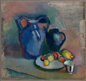 <p>This roughly two-foot square oil still life features a jug, a tall teapot, a plate of fruit, and a small white teacup. The large, blue, double-handled jug stands to our left of center, and the smaller blue teapot stands to its right. In front of the teapot is a white plate which features several round pieces of orange and yellow fruit. To the right of the plate, in the lower right hand corner, is the delicate, fluted teacup. The brushstrokes and colors are lush, bold and clear in the subjects, but much softer and more blended in the muted background. The subjects have been rendered with three-dimensionality, featuring shadows beneath the plate and teacup, and bright spots on the jug and teapot where light appears to fall; but the table on which the objects presumably sit has not been fully realized. Spotty, thin, gray paint covers the upper right hand corner of the canvas, and the blended patches of pastel greens and coral that surround the subjects are dry and muted by comparison.</p>