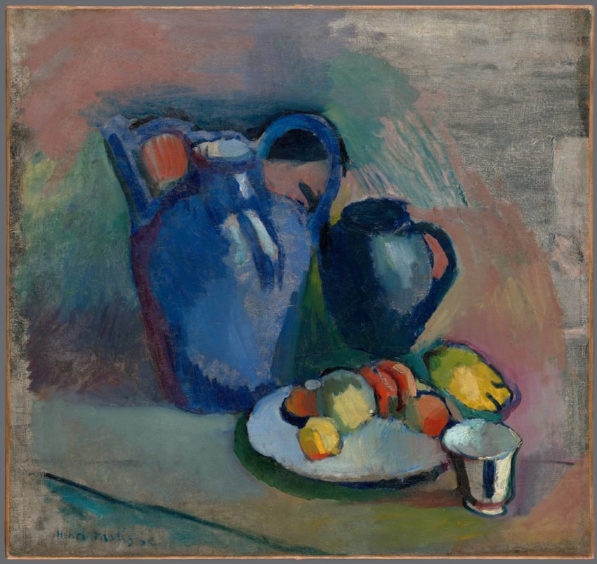 This roughly two-foot square oil still life features a jug, a tall teapot, a plate of fruit, and a small white teacup. The large, blue, double-handled jug stands to our left of center, and the smaller blue teapot stands to its right. In front of the teapot is a white plate which features several round pieces of orange and yellow fruit. To the right of the plate, in the lower right hand corner, is the delicate, fluted teacup. The brushstrokes and colors are lush, bold and clear in the subjects, but much softer and more blended in the muted background. The subjects have been rendered with three-dimensionality, featuring shadows beneath the plate and teacup, and bright spots on the jug and teapot where light appears to fall; but the table on which the objects presumably sit has not been fully realized. Spotty, thin, gray paint covers the upper right hand corner of the canvas, and the blended patches of pastel greens and coral that surround the subjects are dry and muted by comparison.