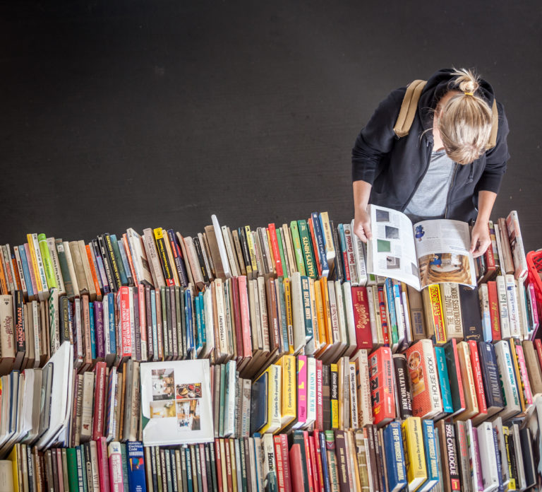 person looking through several book from bird's eye view
