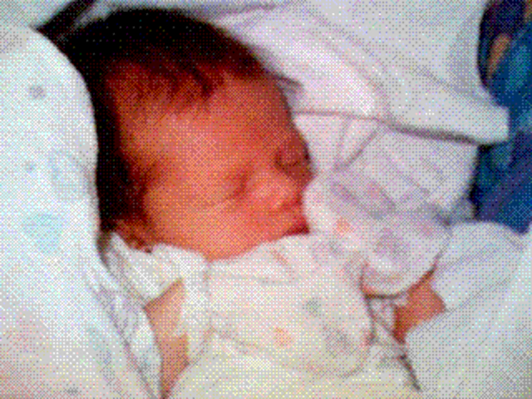 photograph of a baby in heart print clothing and blanket