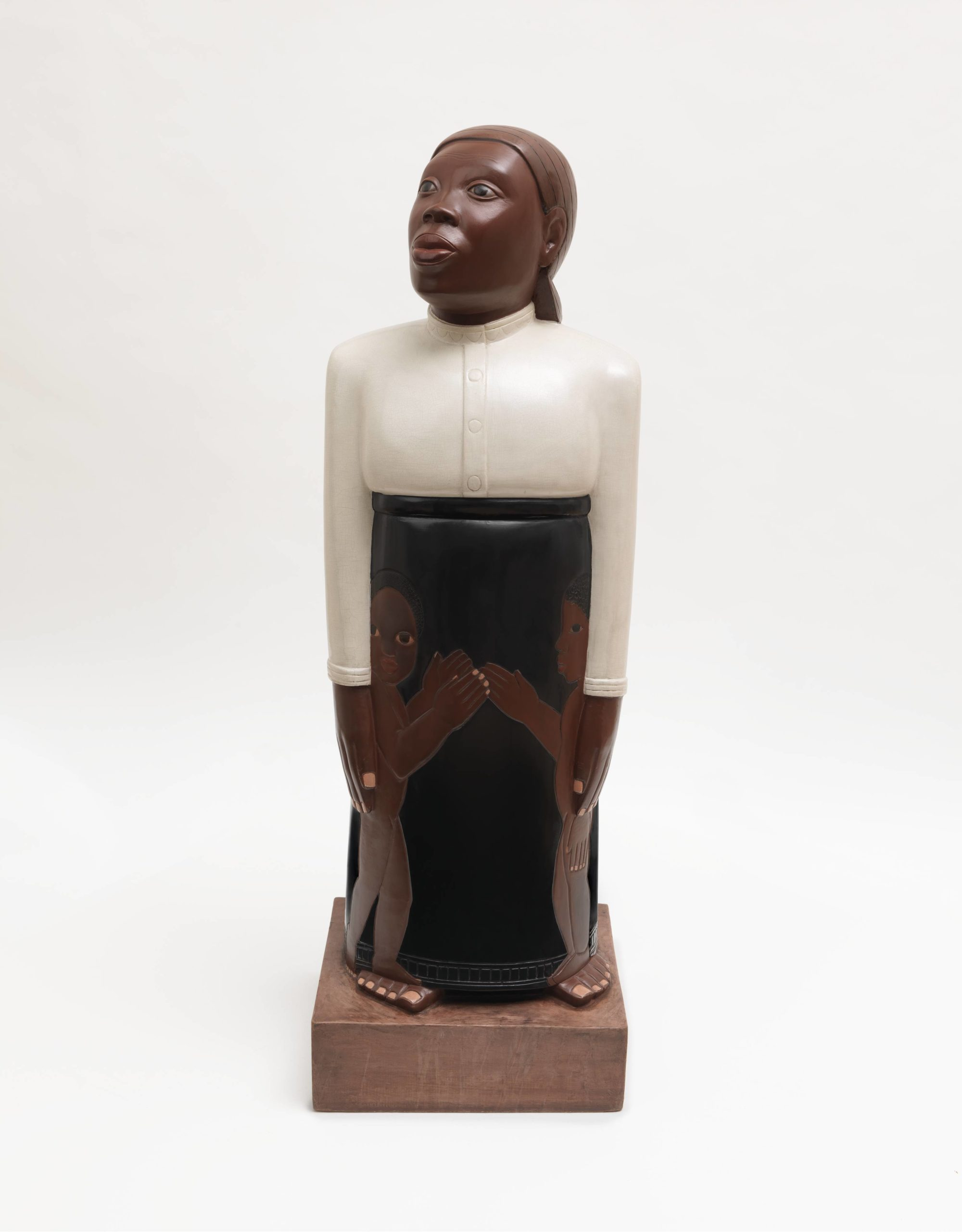 This three foot tall painted wooden sculpture depicts a wide-eyed black woman, standing tall with her hands at her side. Wearing a floor-length black skirt, a modest white blouse, and her hair tied back, the woman stands rigidly straight with her chin raised, gazing slightly upward. Her body is smooth and slightly stylized with an exaggerated cylindrical shape, but the features of her face have been realistically carved and painted. Partially covered by her hands are two nude [black] children that have been painted and carved in relief on the front her skirt. They stand in profile, reaching for each other, although the child on our left looks directly at us.
