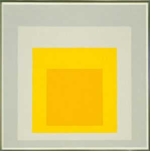 This square oil painting on Masonite pressed fiberboard, approximately two feet wide by two feet tall, features four nested squares of different colors. At the heart of the painting, centered in the lower third of the composition, is a solid golden square. Successively larger squares surround it, creating a series of uniform frames. Moving from the smallest to the largest, the next square, or frame, is school bus yellow, followed by a square of light grey. The largest square is darker grey: the color of dry concrete. A thin, off-white border marks the edge of the painting, and could be considered a fifth square. While each square is distinct and rendered with hard edges, the colors involved are somewhat ambiguous, due to the influence that the adjacent colors have on one another. Their placement, while clearly delineated each within the other, is also ambiguous: diminishing squares can give the appearance of either advancing or receding, as the two yellow and gold squares in the center can seem to pop out towards us while the two gray squares that surround them recede; on the other hand, the dark golden central square can also be construed as if seen through a tunnel, in the distance. This square oil painting on Masonite pressed fiberboard, approximately two feet wide by two feet tall, features four nested squares of different colors. At the heart of the painting, centered in the lower third of the composition, is a solid golden square. Successively larger squares surround it, creating a series of uniform frames. Moving from the smallest to the largest, the next square, or frame, is school bus yellow, followed by a square of light grey. The largest square is darker grey: the color of dry concrete. A thin, off-white border marks the edge of the painting, and could be considered a fifth square. While each square is distinct and rendered with hard edges, the colors involved are somewhat ambiguous, due to the influence that the adjacent colors have on one another. Their