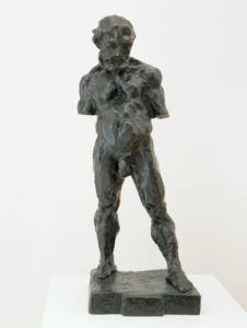 This three foot tall cast bronze statue depicts a stocky nude man with arms truncated above the elbow. The man stands on a square bronze plinth with his feet shoulder-width apart, and his left foot ahead of the right. His head is slightly oversized, with wavy hair, a strong brow, and a full beard. Chin to chest, he stares in the direction of his forward foot with a neutral expression. He has thick, chunky muscles in his legs, chest, neck and shoulders, and his scrotum hangs heavy and low. The charcoal-colored cast bronze appears modeled by hand like soft clay, with deep finger marks covering the surface.