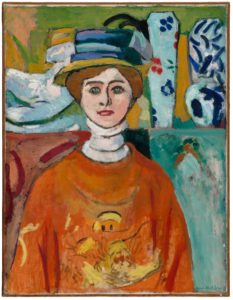 <p>This two foot tall, one-and-a-half foot wide oil portrait features a woman in an orange shawl and blue hat in front of a row of ceramics. The woman faces us, just to our left of center, wearing a pleasant but neutral expression. Her skin is pink, her lips are red, and her eyes are wide and teal green. Her long neck is covered with a tiered white turtleneck, and draped over her sloping shoulders is a bright orange shawl adorned with an indiscernible yellow image. Behind the woman, at the level of her head, are several ceramic pieces, rendered with the same focus and soft detail as the subject herself. To our left is an abstract piece, and to the right are tall decorative vases, all in blues ranging from icy to indigo. Despite the intense stare of the woman's green eyes, the painting's focus is shared by the multiple patterns, bright colors, and disparate design elements.</p>