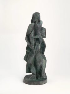 In this three foot tall bronze sculpture, the elements of a human figure have been broken down into abstracted composite shapes. With visible tool marks and hints of green patina, the figure stands on a round plinth. The figure's knees are bent and bowlegged, and her feet resemble thick wedges. She appears to be wearing a long, heavy coat, and her segmented arms fold across her torso cradling a collection of angular objects. The angular planes of the figure's face are smooth and featureless, save for carved almond-shaped outline representing the right eye. A wavy wig-like shape completes the back of the head helping to suggest the representational figure in the abstract form.