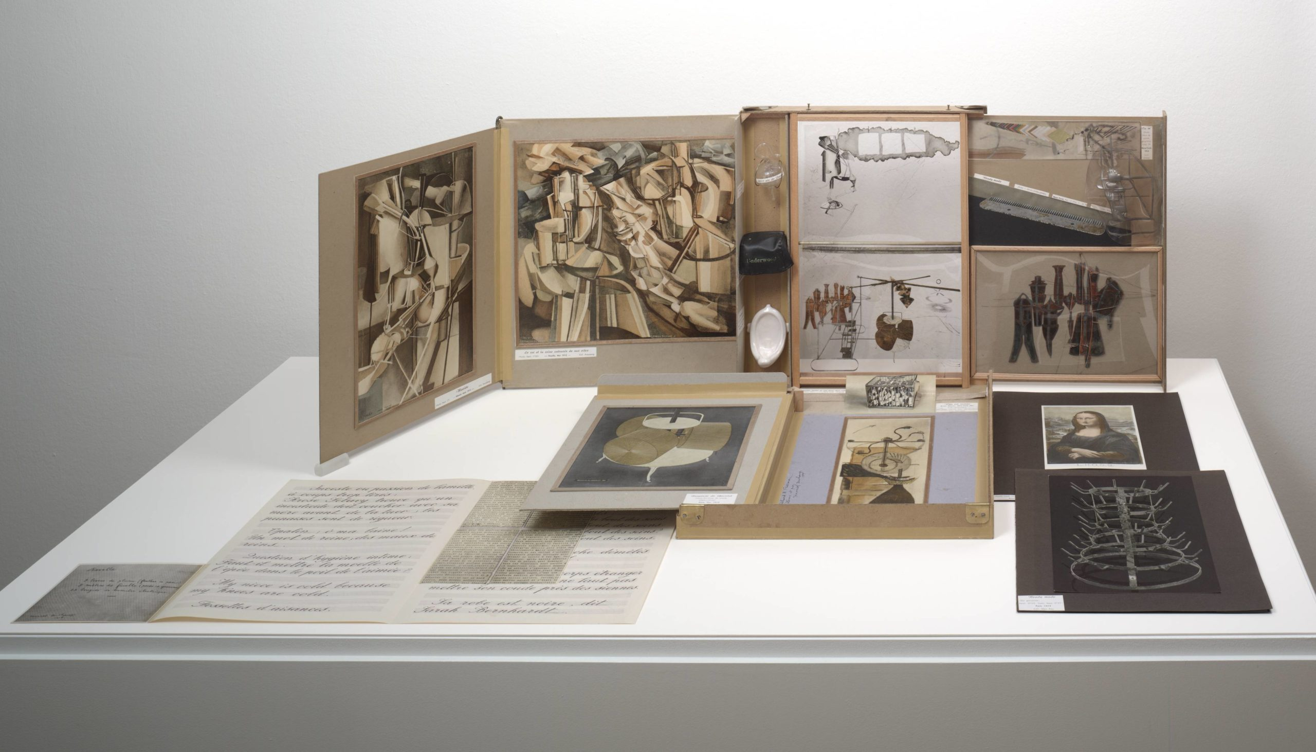 This work consists of dozens of reproductions, some sculptural, but most on paper, which can be stacked, bundled up, and stored in a cardboard box that fits inside a brown leather valise. When the valise is opened, several panels unfold from within to create, in essence, the walls of a small, portable museum. Miniatures of the artist's most famous sculptures are displayed in this tiny gallery, including 'Fountain', and '50cc air de Paris'. On the unfolded walls are prints of some of Duchamp's Cubist paintings, and photographs of elaborate sculptures. Additional prints and sheets of handwritten text can be removed from the valise and displayed lying flat, or standing upright on folding frames that resemble greeting cards. The loose pieces include a photo of Duchamp's sculpture 'Bottle Rack', and a [doctored] print of Leonardo da Vinci's 'Mona Lisa'.