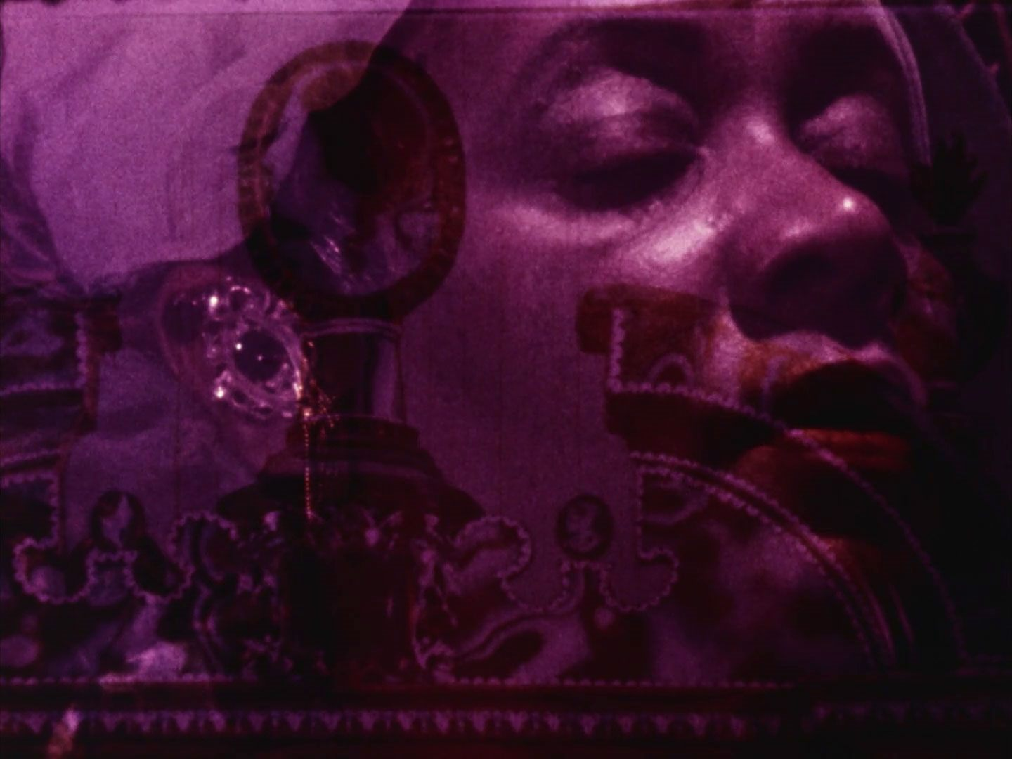 Artistic film still depicting a woman's face overlayed with the sillouettes of decorative antiques.
