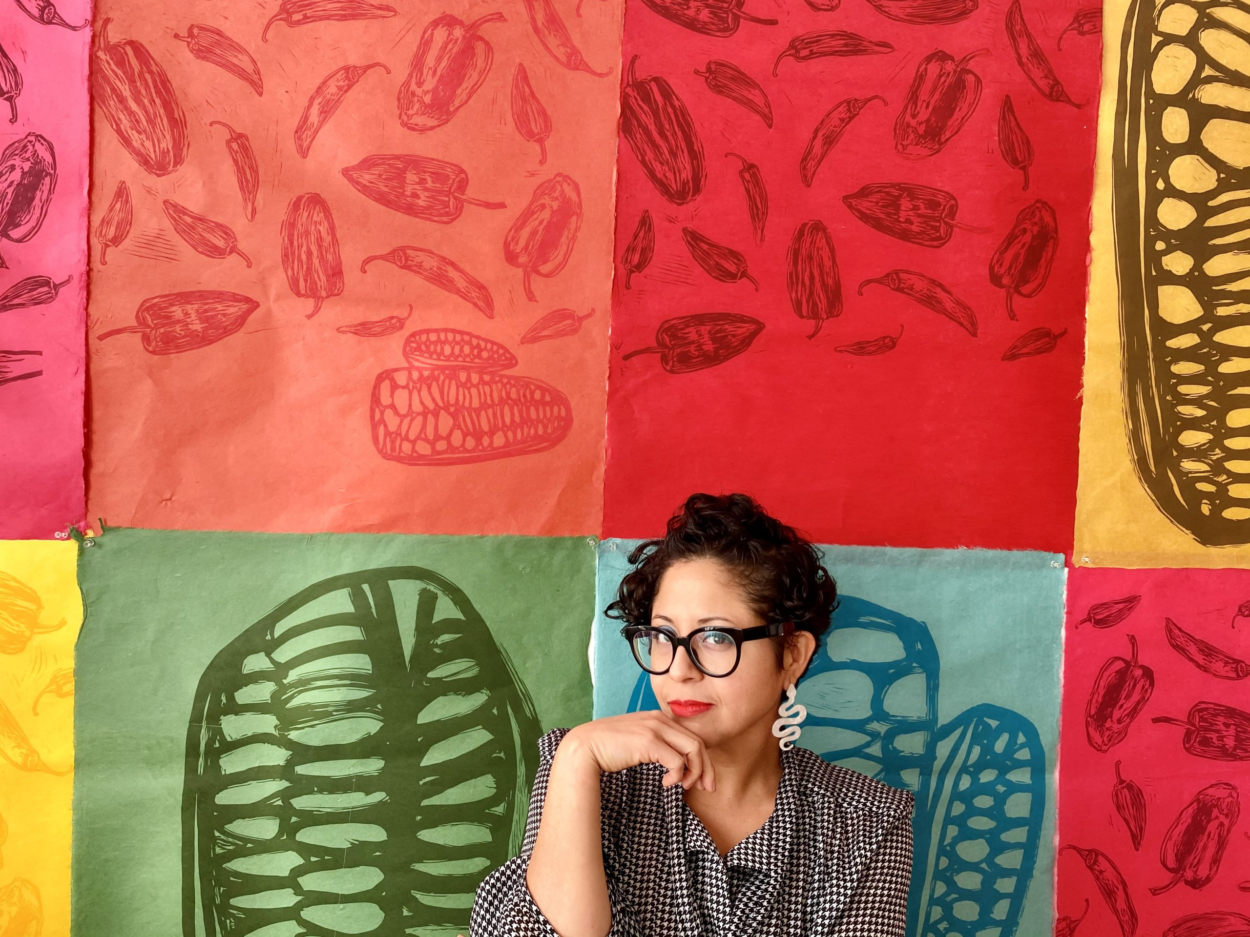 Headshot of Favianna Rodriguez in front of colorful artwork.