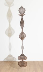 """This vertical hanging sculpture is almost eleven feet tall, and features six lobes of delicate """"crocheted' mesh, crafted with wire made from iron, copper, and brass. The continuous, undulating form resembles a mesh tube that has been pinched in some places, and stretched in others, to create a series of symmetrical, but irregularly sized orbs. Some of the resulting shapes resemble bulbous onions, almost two feet in diameter, with domed tops that taper to a point. Others are much thinner, like elongated cocoons that taper at both ends to a width of mere inches. The uppermost lobe has an onion-dome top, and a collar at its base that is shaped like a tea cup saucer. Beneath that, near the middle of the sculpture, are two orbs with multiple layers. Each contains a second pod with a wire mesh sphere inside, not unlike a yoke inside an egg, floating in a basket. A long, stretched cocoon of wire mesh hangs beneath the first three lobes, linking them to a cluster of orbs at the bottom of the sculpture. These overlapping shapes resemble two distorted hourglasses. A single sphere is suspended inside the top lobe of this bottom grouping."""